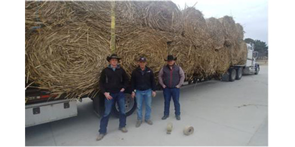 NCTA students Garison Fisher of Beaver City (left) and Cole Sundquist of Ainsworth (right), greet Leon Kuhn (center) who trucked the donation from Kansas as he made the first hay delivery to NCTA. (C. Hauptman/ NCTA photo)