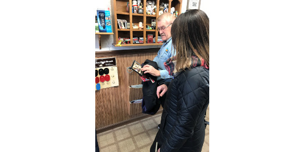 Julie Falk of Hankinson chats with Park River barber George Moen when a group of Hankinson residents makes an unannounced visit to Park River as part of NDSU Extension's Community Impressions program. (NDSU photo)