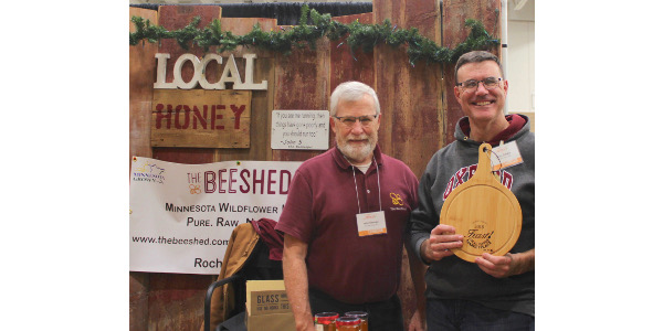 Co-owners of The Bee Shed, John Shonyo and Chris Schad, pose with the FEAST! 2018 People's Choice engraved cheeseboard at the event in Rochester, Minn. last December. (Courtesy of Elena Byrne)
