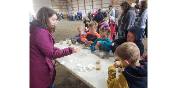 Activities like creating seed germination necklaces at the Davis Family & Friends Agriculture Day help teach students about important agricultural commodities like corn and soybeans. These crops are used for human food, turned into hundreds of products, and also used for cattle, swine, and poultry feed. (Courtesy of Iowa Agriculture Literacy Foundation)