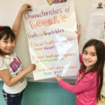 Students from Cora B. Darling Elementary School in Postville, Iowa, show off a local foods poster they helped create. (Photo by Claire Anderson, FoodCorps Iowa)