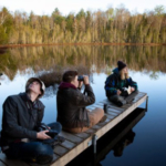 From left, UW–Madison students Grant Witynski, Mace Drumright, and Abby Haydin, conduct a bird playback survey on a small lake at Kemp Natural Resources Station near Minocqua, Wis., early Thursday morning, May 23, 2019. The students were taking Forest and Wildlife Ecology 424: Wildlife Ecology Summer Field Practicum, a class held every other year at the station. The survey, which helps the students inventory wildlife populations on their assigned parcel of land, involves playing a selection of bird calls on a small portable speaker, then listening and watching for birds in the immediate area. (Photo by Michael P. King/UW–Madison CALS)