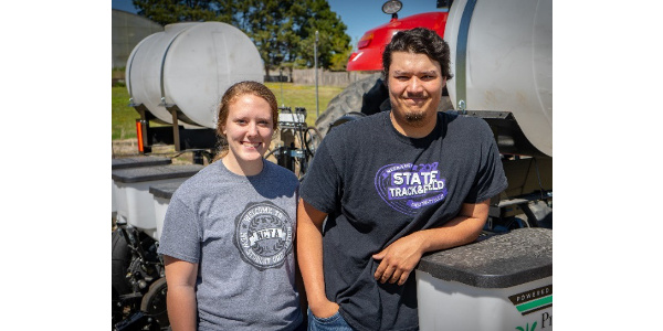 Two students with a new row-crop planter for the NCTA farm. (Cy Cannon / NCTA photo)
