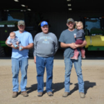 May 2019 marks 100 years the Bainbridge family has farmed near Ethan. Three generations pictured here include: Matt, 38 and his son, Zach, 7 months; Lewis, 69 and Neal, 35, and his youngest daughter, Greta, 2. The Bainbridge's raise soybeans, corn and small grains, and manage a cow/calf and backgrounding operation. (By Lura Roti for SDSRPC)
