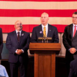 Gov. Ricketts (podium), NDVA Director John Hilgert (right), NeSPA Executive Director Nate Blum (center left), and Humanities Nebraska Executive Director Chris Sommerich (far left). (Courtesy of Office of Governor Pete Ricketts)
