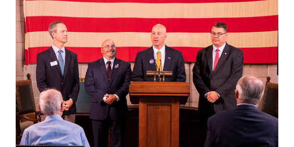 Gov. Ricketts (podium), NDVA Director John Hilgert (right), NeSPA Executive Director Nate Blum (center left), and Humanities Nebraska Executive Director Chris Sommerich (far left). (Courtesy of Office of Governor Pete Ricketts)