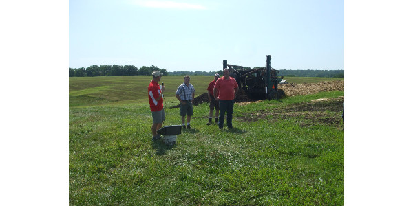"Host of the Farmers of the Sugar River's ""No Till on a Dairy,"" Dan Truttmann, introduces himself and family, while Jason Fuller of Carbon Cycle Consulting, on far right, is ready to explain the compost windrow that is about to be turned in the background. (Courtesy of Green County Land and Water Conservation Dept.)"