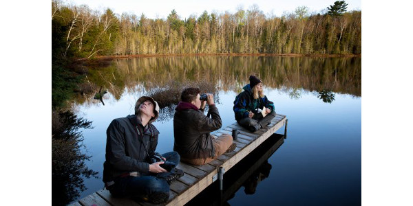 From left, UW–Madison students Grant Witynski, Mace Drumright, and Abby Haydin, conduct a bird playback survey on a small lake at Kemp Natural Resources Station near Minocqua, Wis., early Thursday morning, May 23, 2019. The students were taking Forest and Wildlife Ecology 424: Wildlife Ecology Summer Field Practicum, a class held every other year at the station. The survey helps the students inventory wildlife populations on their assigned parcel of land, and involves playing bird calls on a small portable speaker, then listening and watching for responses. (Courtesy of UW-Madison)