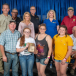 Greene County Farm Family 2019 in front row (Left to right) Joey, Brigid, Julie, and Jessica Wood of Fair Grove. Back Row: Left to Right Dignitaries: Marshall Stewart, Vice Chancellor for MU Extension & Engagement, & Chief Engagement Officer, UM System; Blake Hurst, President, Missouri Farm Bureau; Nikki Cunningham, Missouri State Fair Commissioner; Christopher Daubert, VC and Dean, MU College of Agriculture, Food and Natural Resources; Christine Chinn, Director, Missouri Department of Agriculture; Ted E. Sheppard, Missouri State Fair Commissioner; (Seated) Lowell Mohler, Missouri State Fair Commissioner. (Courtesy of David Burton)