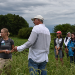 Paul Mugge (in white) discussing a hairy vetch breeding project with Lisa Kissing Kucek of the USDA-ARS Dairy Forage Research Center and others at a field day on his northwest Iowa farm. (Photo courtesy of Practical Farmers of Iowa)