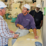 Shawn Thiele, flour milling and grain processing curriculum manager and associate director at the IGP Institute shows participants product streams from the purifiers to understand proper function and set-up. (Courtesy of KSU)