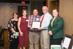 Pam and John Barnes of Tri-County Electrical Contractors, second and third from left, receive the Naomi Crouch 4-H Volunteer Leadership Award from Louella Pryor, left, Chuck Pryor, second from right, and 4-H State Council President Heather Snow, right. Photo by Casey Buckman.