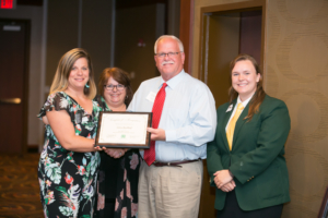 Cara Riekhof, left, receives the Naomi Crouch 4-H Volunteer Leadership Award from Louella and Chuck Pryor, center, and 4-H State Council President Heather Snow, right. Photo by Casey Buckman.