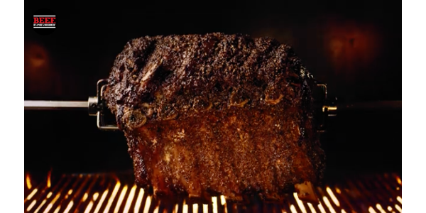 The Beef Drool Log is a two-and-a-half-hour video featuring a Prime Rib Roast cooking on a rotisserie over an open flame. (screenshot from video)