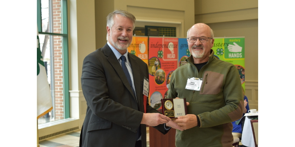 Rick Jorgenson, North Dakota's Outstanding Lifetime 4-H Volunteer for 2019 (right) receives a gift from Lyndon Anderson, a North Dakota 4-H Foundation board member. (NDSU photo)